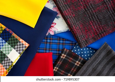 Fabric of different colors. Fabric waiting for sewing clothes and other things. Checkered, blue, red, yellow fabric. View from above. Fabric suit, knitted, jersey, gabardine. The cloth.