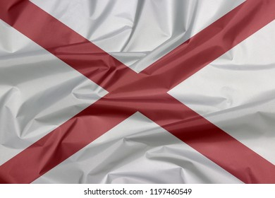 Fabric flag of Alabama. Crease of Alabama flag background, The states of America,  Red St. Andrew's saltire in a field of white.