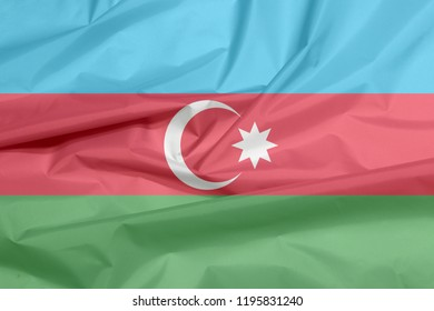 Fabric flag of Azerbaijan. Crease of Azerbaijani flag background, blue, red, and green, with a white crescent and big star.