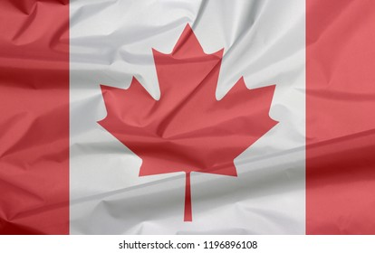 Fabric flag of Canada. Crease of Canadian flag background, a vertical triband of red and white with the red maple leaf.