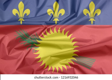 Fabric flag of Guadeloupe Local. Crease of Guadeloupe Local flag background. red field with yellow sun and green sugar cane, and a blue stripe with yellow fleurs-de-lis on the top.