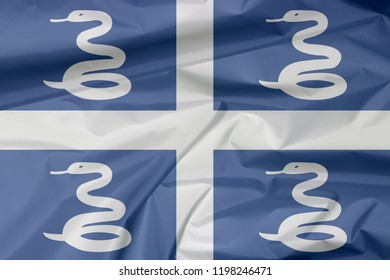 Fabric flag of Martinique. Crease of Martinique flag background, Four white snake on blue field and white cross in the center.