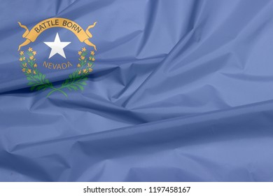 Fabric flag of Nevada. Crease of Nevada flag background, The states of America, two sagebrush branches encircling a silver star with text Nevada and Battle Born.