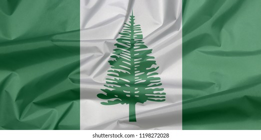 Fabric flag of Norfolk Island. Crease of Norfolk flag background, Norfolk Island Pine in a central white stripe between two green stripes.