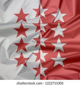 Fabric flag of Wallis. Crease of Valais flag background, The canton of Switzerland Confederation.