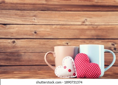 Fabric hearts with cups on brown wooden table