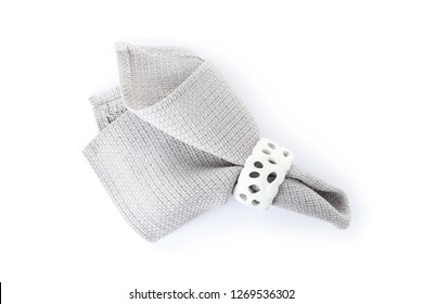 Fabric napkin with decorative ring for table setting on white background