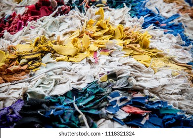 Fabric scraps, old clothing and textiles are cut into strips and grouped tightly together, forming layers of disheveled cloth. Closeup design resembles up-cycled textile, blanket, rug or pillow.
