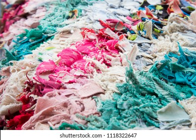 Fabric scraps, old clothing and textiles are cut into strips and grouped together, forming diagonal rows of disheveled pieces of cloth. Closeup design resembles an up-cycled blanket, rug or pillow.
