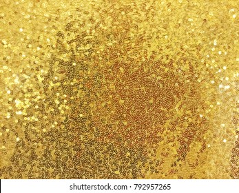 Fabric Sequins in bright Colors. Fashion Fabric with glitter,  Fabric is light closeup. Yellow Fabric Sequin. Golden Background.