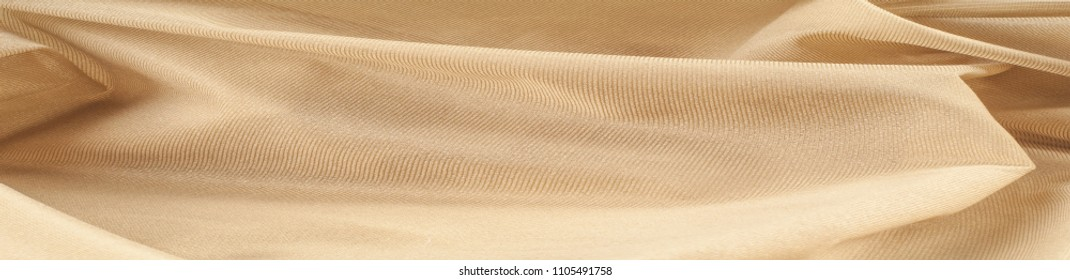 Fabric silk texture, cream, cream-colored, cream-coloured, pale beige. a fine, strong, soft, lustrous fiber produced by silkworms in making cocoons and collected to make thread and fabric.