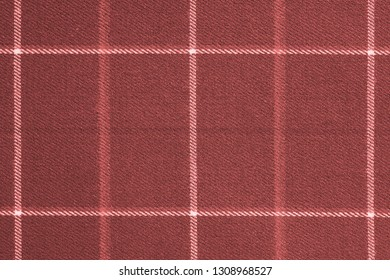 fabric or textile material with a checkered pattern closeup for a fashionable background or for wallpaper of living coral color