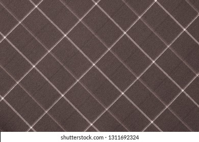 fabric or textile material with a checkered pattern closeup for a fashionable background or for wallpaper of brown toffee color