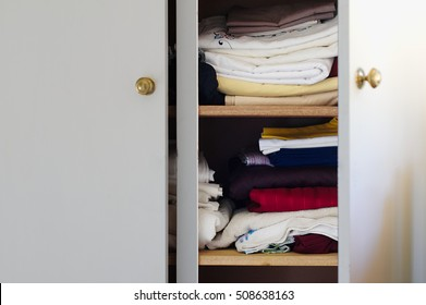 Fabrics And Bed Sheets In Half Open White Closet Or Wardrobe