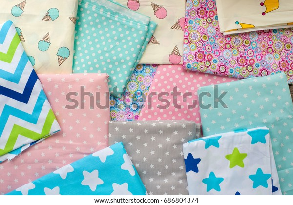Fabrics made of cotton. View from above. Multicolored cotton fabrics are spread out on the table. Cotton fabrics for sewing clothes and bed linen. Sewing and tailoring. Satin and cotton.