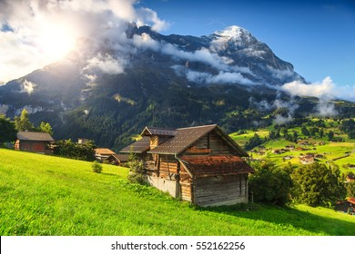Fabulous alpine wooden houses, green fields and famous touristic Grindelwald town with high North Face of Eiger mountains, Bernese Oberland, Switzerland, Europe