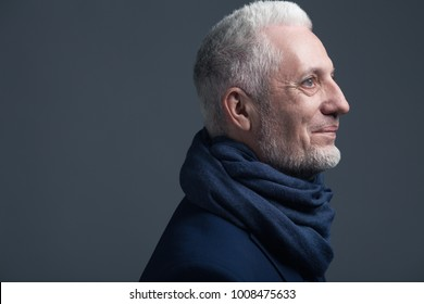 Fabulous at any age concept. Close up portrait of 60-year-old man wearing trendy accessory, standing over gray background. Street style. Copy-space. Studio shot