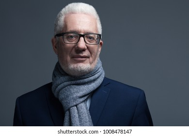 Fabulous at any age concept. Close up portrait of 60-year-old man wearing trendy accessories, standing over gray background. Classic style. Copy-space. Studio shot