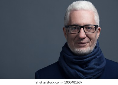 Fabulous at any age concept. Close up portrait of 60-year-old man wearing trendy accessories, standing over gray background. Street style. Copy-space. Studio shot