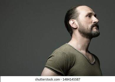 Fabulous at any age concept. Profile portrait of 40-year-old man standing over dark gray background. Hair brushed back. Rocker, biker style. Scar on forehead. Close up. Copy-space. Studio shot