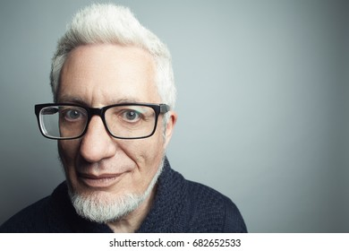 Fabulous at any age, Eyewear concept. Portrait of fashionable 60-year-old man in blue sweater over gray background. Trendy haircut, glossy grey hair. Copy-space. Close up. Studio shot