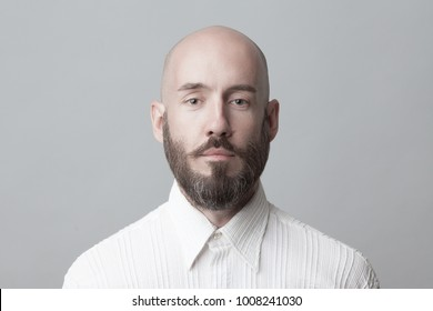Fabulous at any age. Portrait of 40-year-old man standing over light gray background in white shirt. Close up. Classic style. Bald shaved head. Copy-space. Studio shot