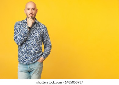 Fabulous at any age. Portrait of 40-year-old vegan man standing over light yellow background in blue shirt, jeans. Good figure. Hipster style. Bald shaved head. Copy-space. Studio shot