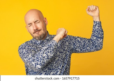 Fabulous at any age. Portrait of 40-year-old dancing man feeling happy over light yellow background in blue shirt. Funny face. Hipster style. Bald shaved head. Studio shot