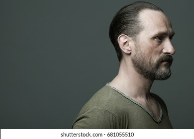 Fabulous at any age. Portrait of 40-year-old man standing over dark gray background. Hair brushed back. Rocker, biker style. Close up. Copy-space. Studio shot