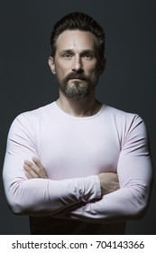 Fabulous at any age. Portrait of 40-year-old man standing over dark gray background. Classic style. Scar on forehead. Hands crossed. Studio shot