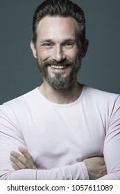 Fabulous at any age. Portrait of laughing 40-year-old man standing over dark gray background with hands crossed. Hipster style. Scar on forehead. Studio shot
