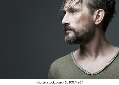 Fabulous at any age. Profile portrait of 40-year-old man with wet hair standing over dark gray background. Long hair on forehead. Rocker, biker style. Close up. Copy-space. Studio shot