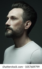Fabulous at any age. Profile portrait of 40-year-old man standing over dark gray background. Close up. Hipster style. Studio shot