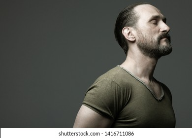 Fabulous at any age. Profile portrait of charismatic muscular 40-year-old man standing over dark gray background. Hair brushed back. Rocker, biker style. Close up. Copy-space. Studio shot