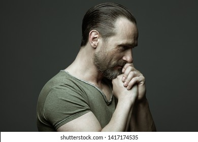 Fabulous at any age. Profile portrait of 40-year-old man praying over dark gray background. Hair brushed back. Rocker, biker style. Hands near face. Close up. Copy-space. Studio shot