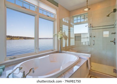 Fabulous bathroom features nook filled with glass shower and tub accented with marble tub deck surround placed under windows overlooking the waters of Lake Washington. Northwest, USA.