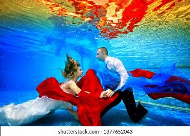 85a73077d65a2 Fabulous bride and groom swim and dance underwater in the pool with red and  blue fabric