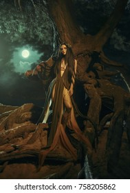 A fabulous, forest nymph with long hair stands in the roots of a tree in the moonlight. Background dark night and fog. Mythical character of Gyana