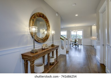 Fabulous foyer features beige colored walls adorned with board and batten and furnished with a wood console table under a round wood mirror illuminated by iron buffet lamps.