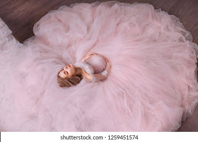 a fabulous magical photo of an attractive pretty pregnant girl with blond hair in a magnificent magnificent pink dress with bare shoulders, the expectant mother closed her eyes and hugs her tummy