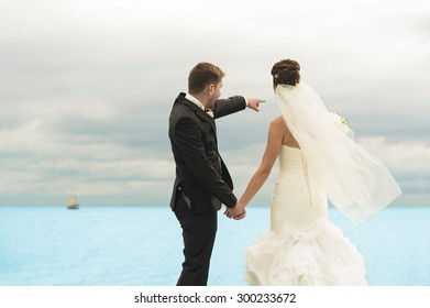 Fabulous newlyweds are standing by the ocean shore. The are admiring the scenery.