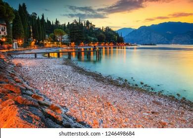 Fabulous place with stunning beach at sunset, Malcesine touristic recreation resort, lake Garda, Veneto region, Italy, Europe
