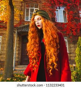 Fabulous redhead woman with long curly hair in a red coat and a green turban on a bright autumn background. Girl on the fabulous background of a building with orange autumn leaves. Fantastic photo