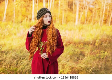 Fabulous redhead woman with long curly hair in red coat on blurred autumn background. Girl on fabulous background of forest with orange autumn leaves. Fantastic photo. Model looking aside. Dry grass