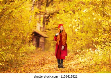 Fabulous redhead woman with long curly hair in red coat on autumn background. Girl on fabulous background of forest with orange autumn leaves. Fantastic photo. Leaves fall from branches. Sunny day
