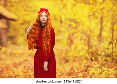 Fabulous redhead woman with long curly hair in red dress on blurred autumn background. Girl on fabulous background of forest with orange autumn leaves. Fantastic photo. Leaves fall from branches.