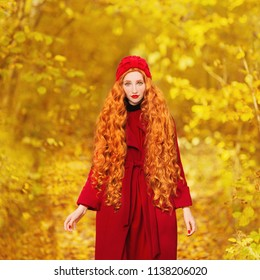 Fabulous redhead woman with long curly hair in red coat on blurred autumn background. Girl on fabulous background of forest with orange autumn leaves. Redhead model. Leaves fall from branches.