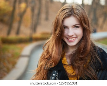Fabulous redhead woman with long hair in yellow sweater black leather jacket on blurred autumn background.