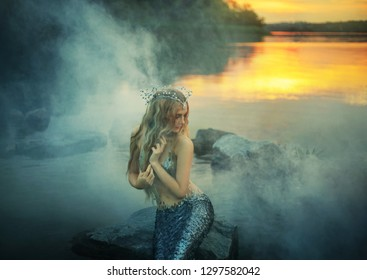 fabulous sea princess modestly looks to the side and combs her long blond blonde hair, dear seashell tiara fits a silvery tail, attractive nymph on the river bank with sun highlights in thick fog