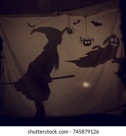 Fabulous shadow little witch with a broom and a Ghost.The theatre of shadows. . Childhood. A magical story.Halloween.